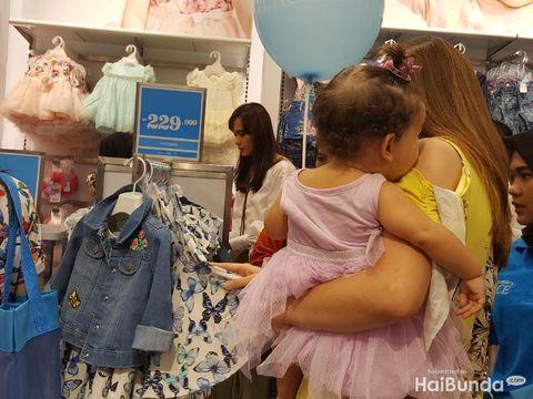 Ibu-ibu sedang belanja baju anak/