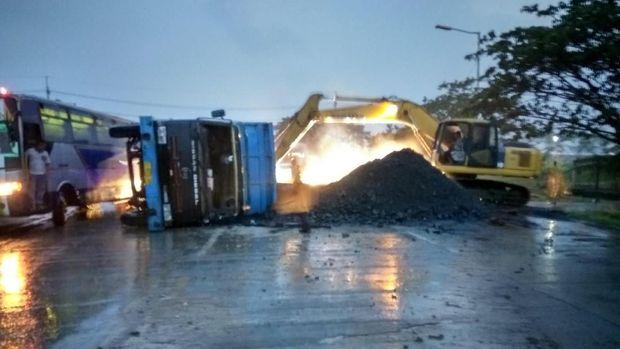 Sebuah backhoe digunakan untuk memindahkan batu bara yang tertumpah