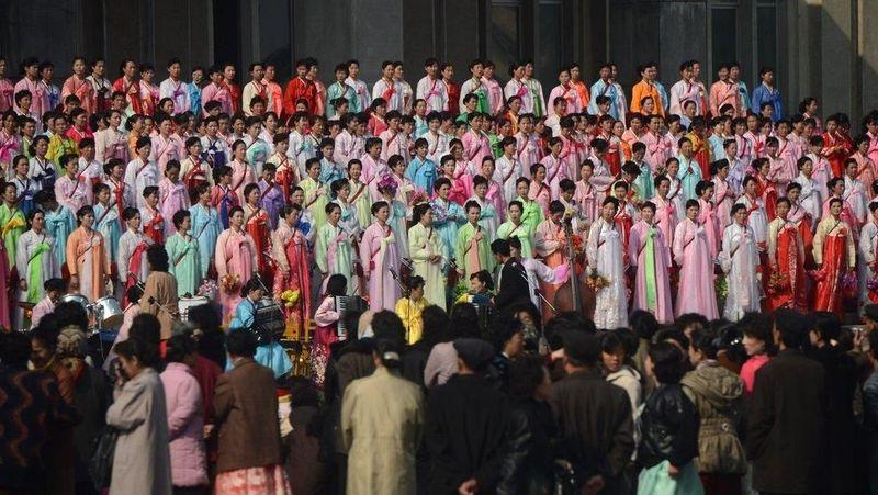 Wanita Korea Utara yang kompak mengenakan pakaian tradisional serta mempraktikkan pertunjukan mereka di jalan-jalan di Pyongyang. Pertunjukan ini sudah berlangsung pada tanggal 11 April 2012 lalu, saat penghitungan mundur ulang tahun ke 100 kelahiran pendirinya, Kim Il Sung (AFP)