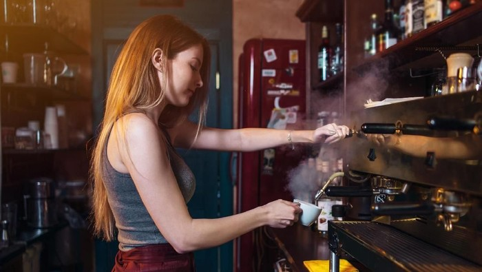 Stylish ginger girl making coffee using a professional coffee machine in coffee house.