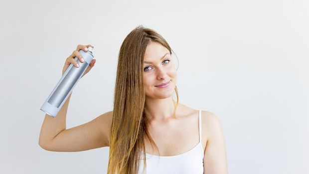 A portrait of a woman styling and drying her hair