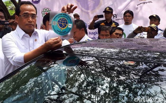 Budi Karya Sumadi menunjukkan stiker taksi online untuk wilayah Jabodetabek.