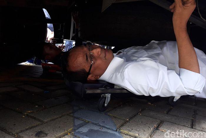 Budi mengecek Iangsung hingga ke dalam kolong Bus Pariwisata.