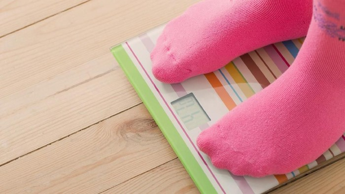 Feet on scales on wooden floor