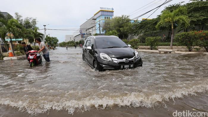 Warga beraktivitas di tengah banjir air laut pasang (rob) di Pelabuhan Nizam Zaman, Muara BAru, Jakarta Utara., Selasa (5/12/2017). Rob tinggi membuat tanggul tidak mampu menahan air laut sehingga membanjiri jalanan setinggi 50 hingg 70an cm. Sejumlah kendaraan roda dua mogok lantaran memaksakan menembus banjir.
