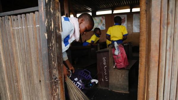 Setelah itu, mereka akan bersama-sama piket untuk membersihkan sampah dari kelas. Fasilitas seperti papan tulis dan spidol sudah melengkapi sekolah ini. (Akintunde Akinleye/Reuters)