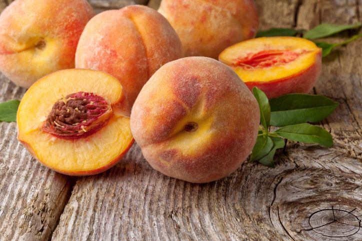 Group of fresh peaches on wooden background