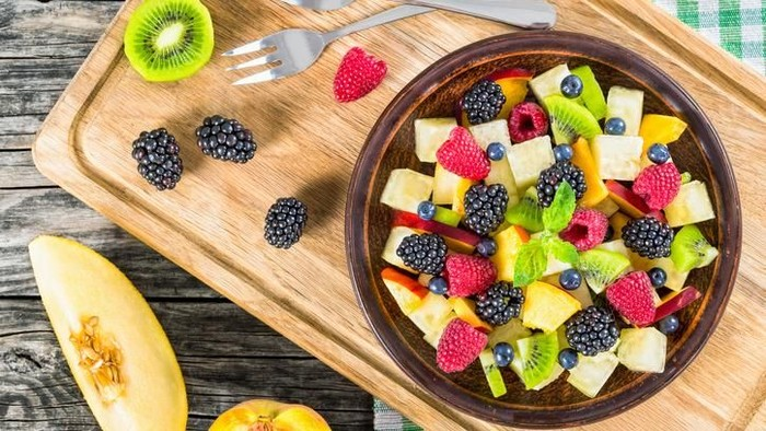 delicious fruit and berry summer salad decorated with mint leaves on clay dish on cutting board with dessert forks, half of peach and slice of melon on rustic boards, view from above