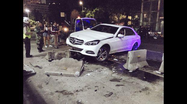 Sebuah mobil sedan putih dengan nomor polisi B 711 MGH menabrak separator busway di Jalan MH Thamrin, Jakarta Pusat