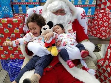 Meskipun sang kakak nangis kencang, adiknya tetap tidur dengan tenang di pelukan Santa. (Foto: Instagram @gmilez71)