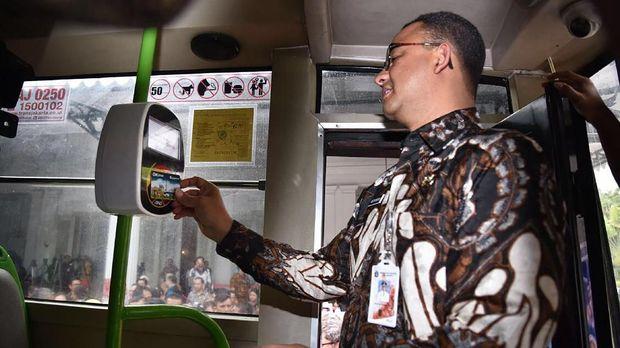 Gubernur DKi Jakarta Anies Baswedan saat mencoba kartu OK Otrip, di Balai Kota DKI Jakarta, Kamis (14/12).