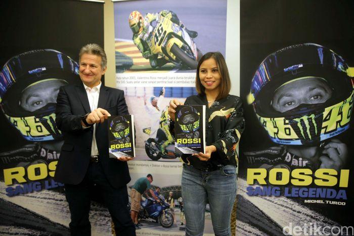 Project Editing Director Dominique Loth (kanan) bersama Deputy Sales and Channel Nadia Helmi (kiri) menunjukkan buku Rossi Sang Legenda pada saat peluncurannya di Jakarta, Kamis (14/12).