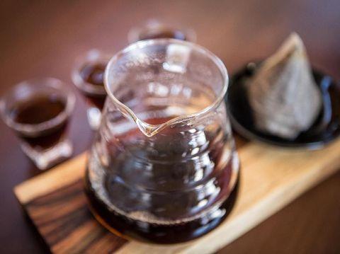 Fresh from the tap nitrous infused dark rich nitro black coffee in a glass jar java creamy beautiful froth foam head lifestyle decor with roasted beans on a rustic reclaimed wood wooden table background