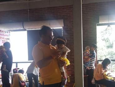 Nah, kalau ini ayah yang menggendong si kecil. Mereka semua kompak berbaju kuning di perayaan ulang tahun anak-anaknya yang pertama, karena mereka berasal dari komunitas Birth Club 2016.