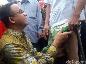 Foto: Saat Anies Pasangkan Kaki Palsu ke Lansia di Monas