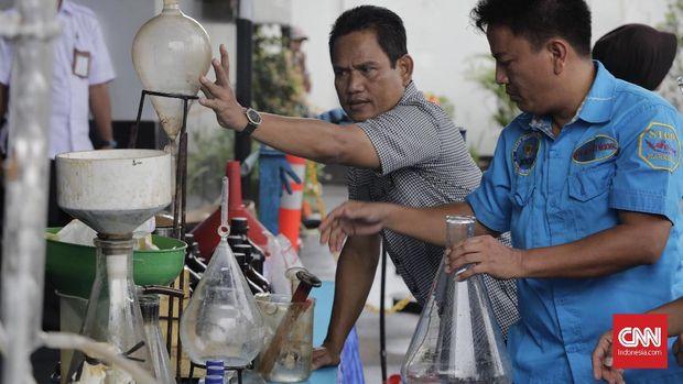 Petugas BNN bersama sejumlah alat produksi narkoba cair di Diskotek MG International Club, Jakarta, Kamis, (21/12/2017).
