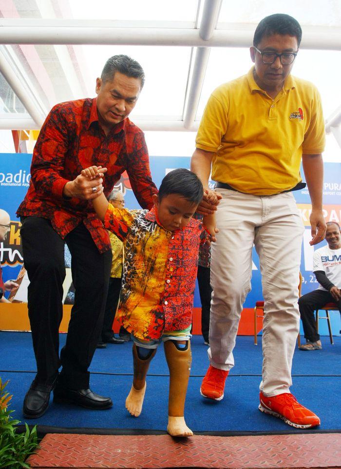 Director of Finance Andra Y Agussalam disaksikan Ketua Kick Andy Foundantion Ali Sadikin dan Eksekutif General Manager Bandara Supadio Jon Mukhtar Rita menuntun Muhammad Athar (4) berjalan. Foto: dok. AP2