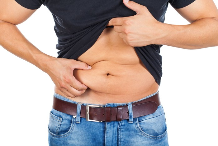 Close up picture of a caucasian young mans fatty abdomen on isolated background. Ilustrasi perut buncit.