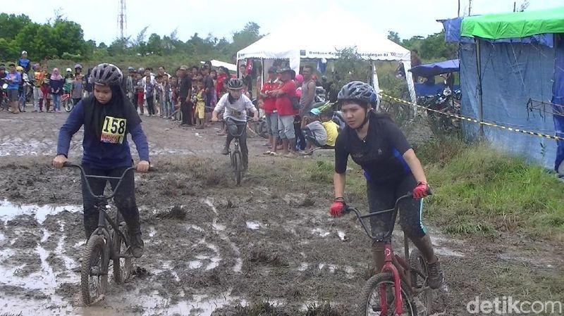 Foto: Mereka beradu cepat menaklukkan trek berlumpur yang cukup berat. Pesertanya, bahkan ada yang wanita dan ada juga yang berhijab. (Deni Wahyono/detikTravel)