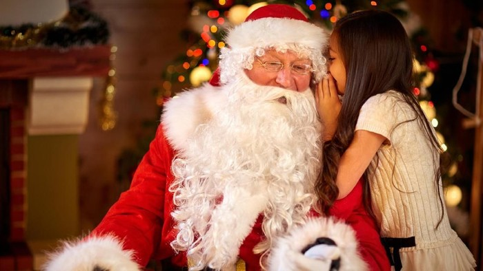 Santa Claus and Little girl,  Christmas Scene. Girl telling wish in Santa Clauss ear in front of Christmas tree