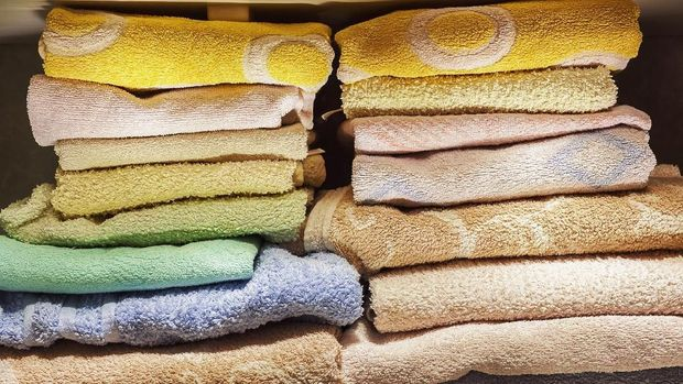 A lot of clean towels on white shelves in bathroom.