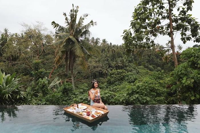 Dengan pemandangan pepohonan hijau, Andien terlihat sedang asyik menikmati sarapan di tengah kolam renang di salah satu hotel di Bali. Foto: Instagram Andien Aisyah