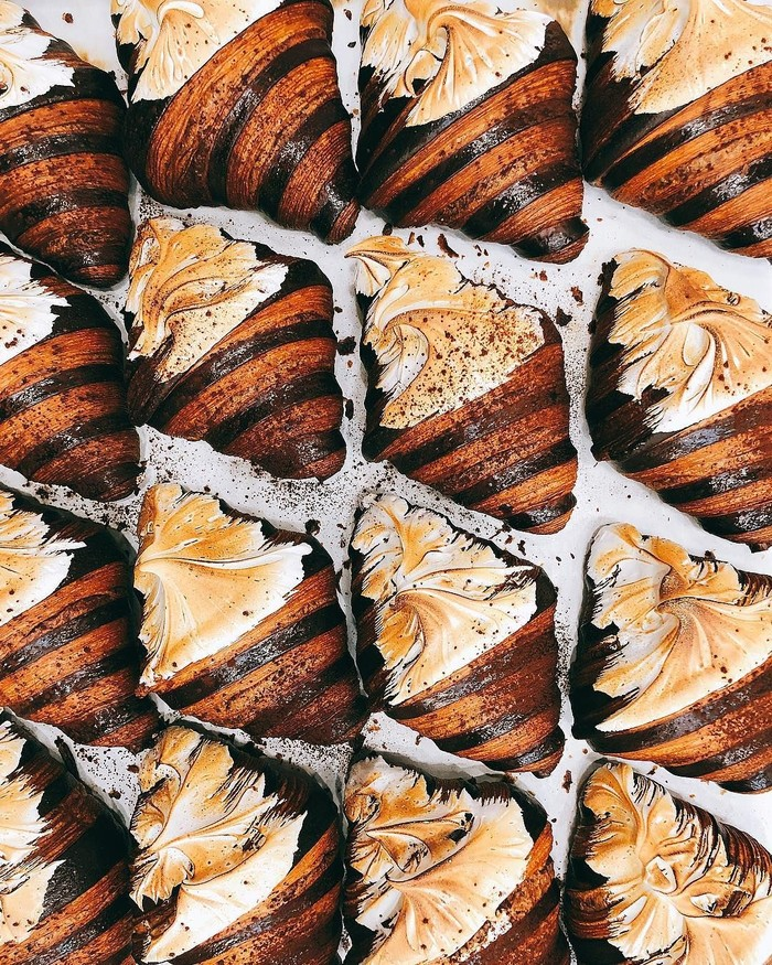 Ciri croissant bi-color adalah warnanya yang belang. Nah yang satu ini varian dengan nama Winter Ferrero Rocher. Croissant warna coklat dengan isi ganache cokelat dan hazelnut. Bagian toppingnya diberi meringue yang di-torch lalu ditaburi bubuk cokelat. Foto: Istimewa