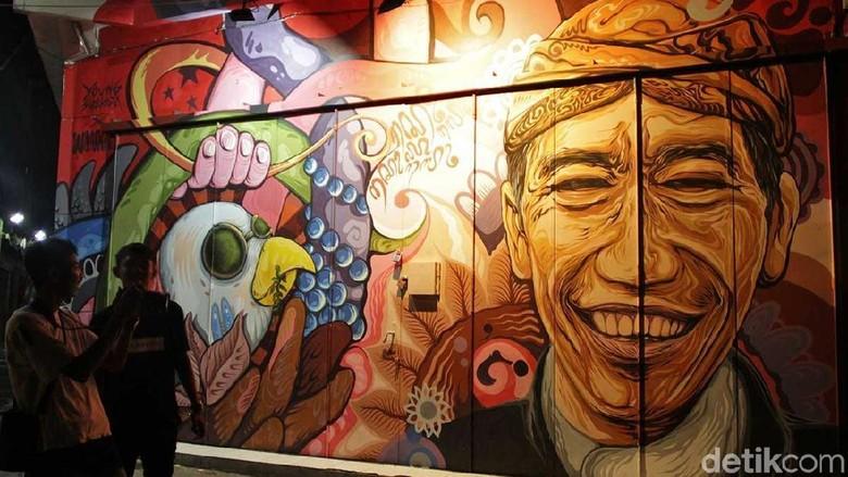Traveler yang tengah melihat mural Jokowi di Solo (Randy/detikTravel)
