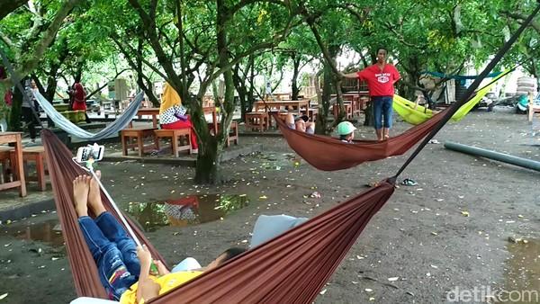 Tak hanya miniatur, ada spot lain yang bisa buat bersantai. Traveler yang datang dari luar Blitar dapat berbaring santai di hammock yang disediakan di bawah rimbunnya pohon belimbing. Pemandangan sawah dan pegunungan pun memanjakan mata (Erliana Riady/detikTravel)