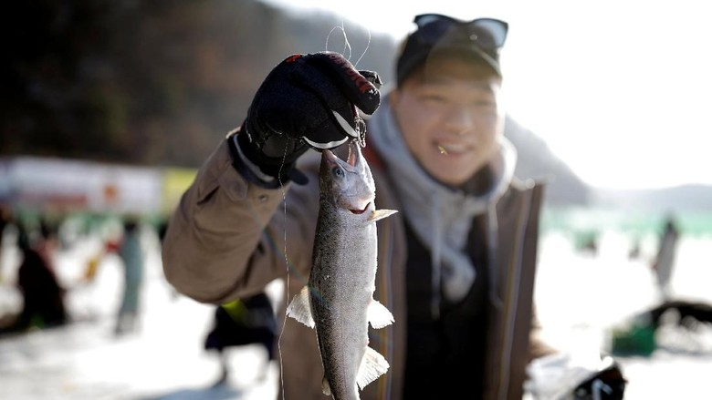 A boy reacts after catching a trout with his hands during an event promoting the Ice Festival in Hwacheon, south of the demilitarized zone (DMZ) separating the two Koreas, South Korea January 6, 2018. REUTERS/Kim Hong-Ji