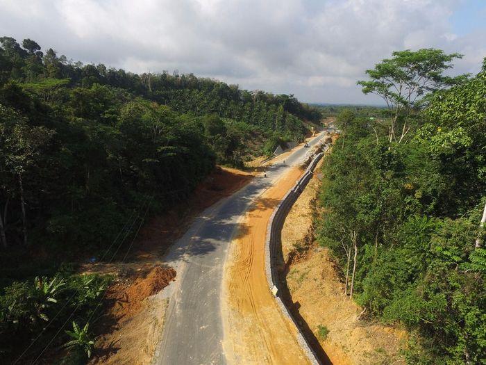 Penampakan jalan Simpang Tanjung-Aruk dari atas udara. Terlihat pemandangan hijau di kedua sisinya. Proses pelebaran jalan telah mencapai 70,206%. Dok. Kementerian PUPR.