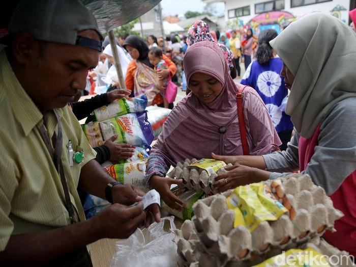 Ratusan warga pemegang Kartu Jakarta Pintar di kawasan Pesanggrahan, Jakarta, antre untuk dapat sembako murah. Warga terlihat sangat semringah.