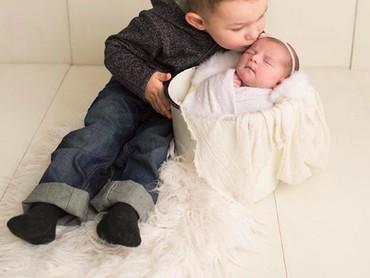 Muah! Wah si kakak mengecup sayang adiknya yang baru lahir nih. So sweet banget ya? (Foto: Instagram/ @hollyschaefferphotography)