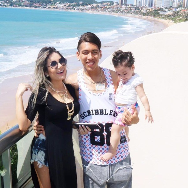 Firmino berpose bersama keluarganya dengan latar belakang panorama pantai yang aduhai (@roberto_firmino/Instagram)