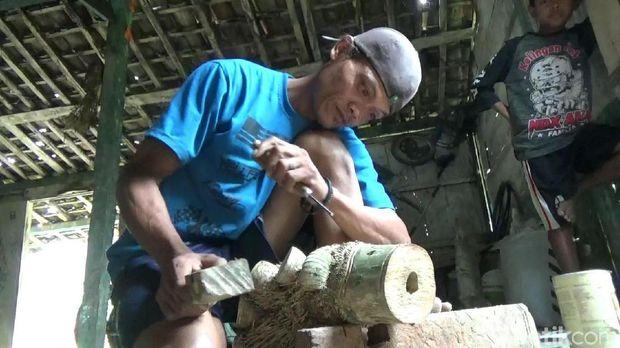 Soim sedang membuat karakter dari bonggol bambu.