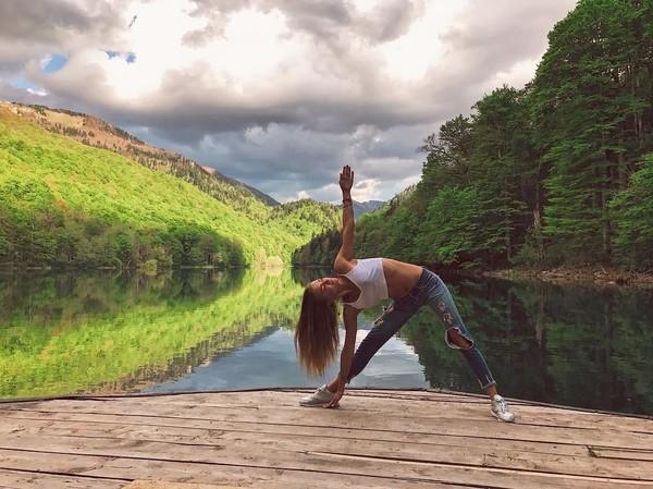 Ia sering mengunggah foto pose yoga dengan latar destinasi wisata yang menawan. Ini foto Ekaterina yoga di Danau Biograd, Montenegro (yogaisdestiny/Instagram)