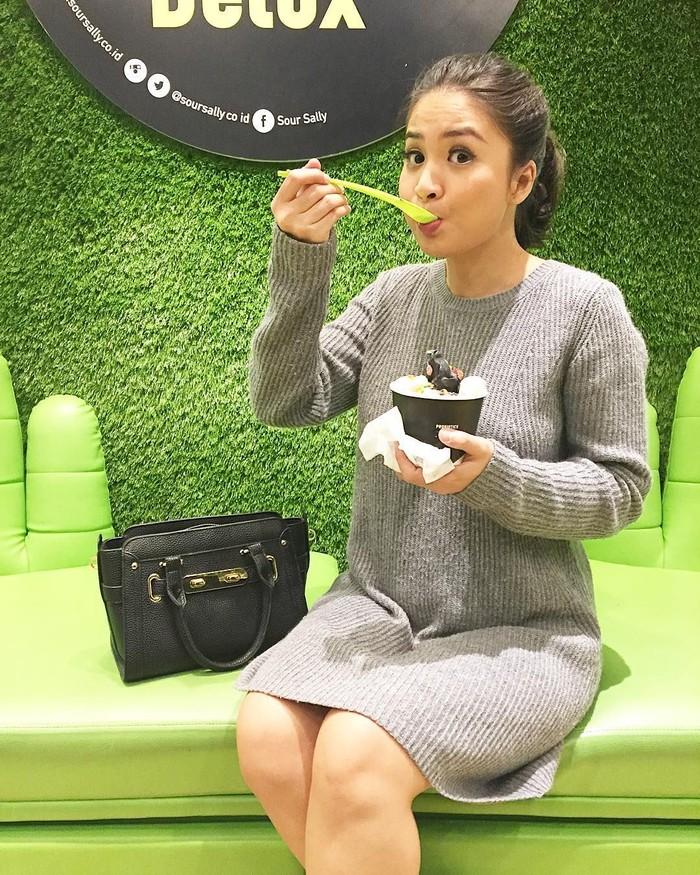 Di salah satu mal di Jakarta, Putri Titian terlihat santai menyantap semangkuk yogurt. Di tangan kirinya ada yogurt sementara tangan kanannya menyuapkan yogurt ke mulutnya. Yumm!
