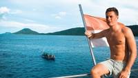 Foto: Stoffel berpose di kapal sambil bertelanjang dada. Sambil memegang bendera Indonesia, dia mengagumi keindahan laut Raja Ampat. (Instagram/@svandoorne)