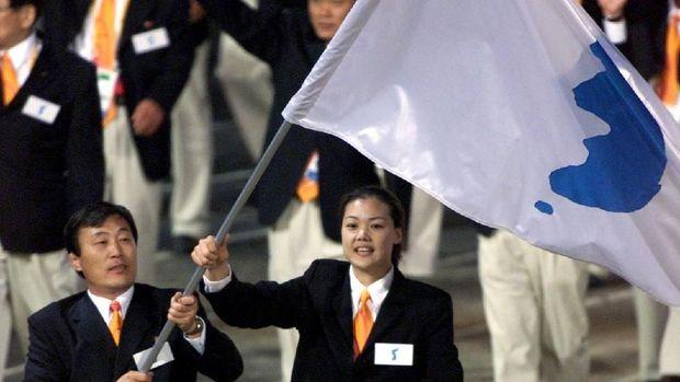 Atlet Korut Jang Choo Pak (kiri) dan atlet Korsel Eun-Soon Chung mengibarkan bendera unifikasi Korea di Olimpiade Sydney, Australia, 15 September 2000.