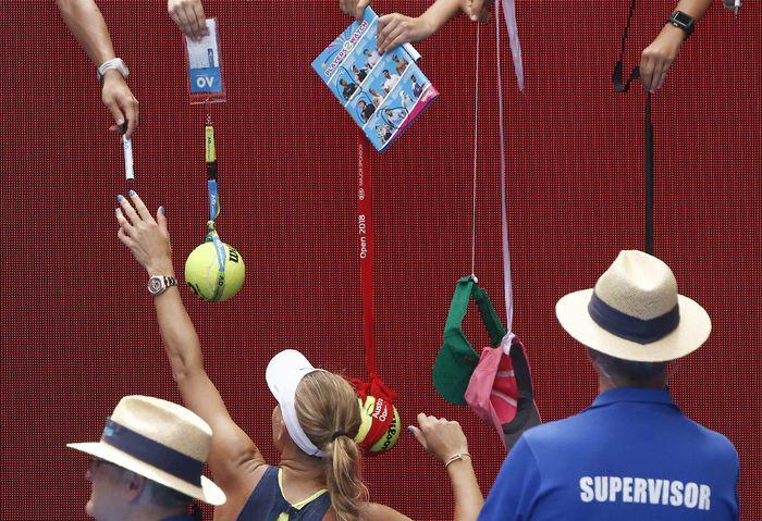 Beginilah salah satu pemandangan umum usai pertandingan di Australia Terbuka. Tampak petenis putri Caroline Wozniacki disodori sejumlah barang untuk ditandatangani. (Foto: Thomas Peter/REUTERS)