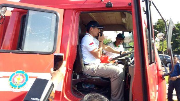 Sandiaga sempat juga mencoba menaiki mobil pemadam kebakaran.