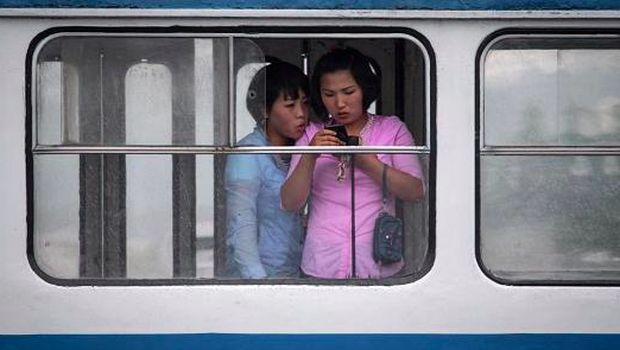 Dua wanita menggunakan ponsel di tram kota Pyongyang, Korea Utara