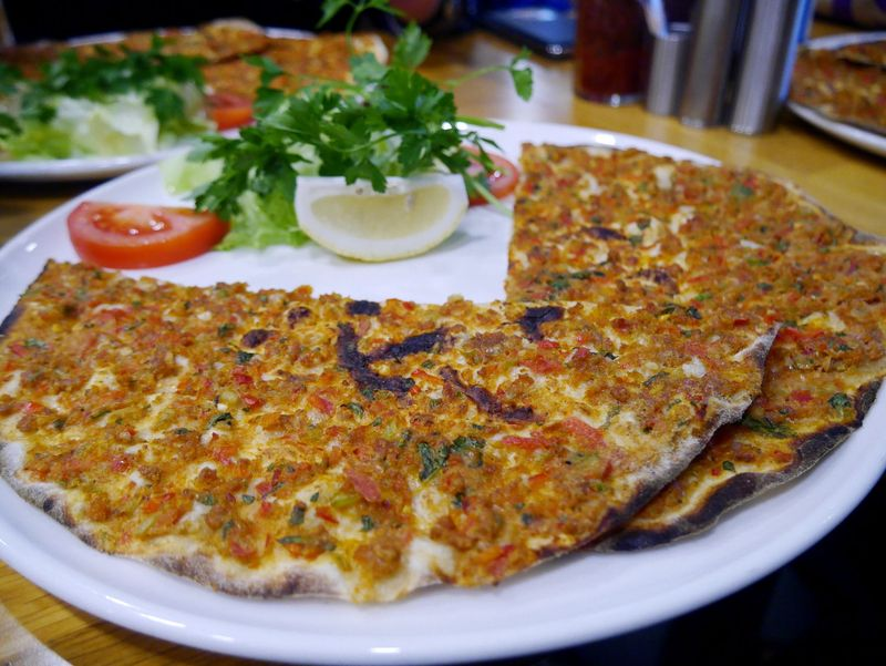 Inilah dia Lahmacun, pizzanya Turki. Lahmacun bentuknya lingkaran yang dibelah dua, disajikan di atas piring putih bersama selada, tomat hingga lemon (Kurnia/detikTravel)