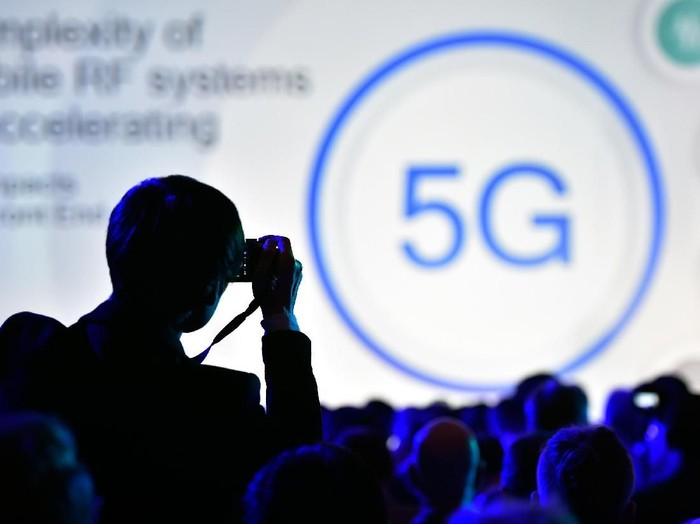 LAS VEGAS, NV - JANUARY 08:  An attendee photographs a 5G logo display during a Qualcomm press event for CES 2018 at the Mandalay Bay Convention Center on January 8, 2018 in Las Vegas, Nevada. CES, the worlds largest annual consumer technology trade show, runs from January 9-12 and features about 3,900 exhibitors showing off their latest products and services to more than 170,000 attendees.  (Photo by David Becker/Getty Images)