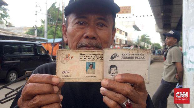 Seorang penarik becak menunjukkan Kartu Anggota Serikat Becak Jakarta.