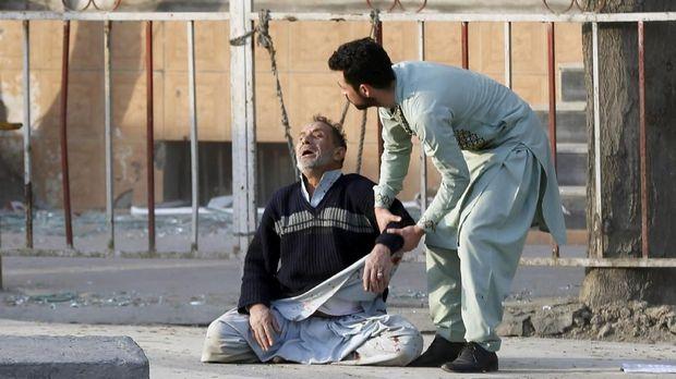 Seorang pria menangisi kematian putranya yang terkena ledakan bom di Kabul, Afghanistan.