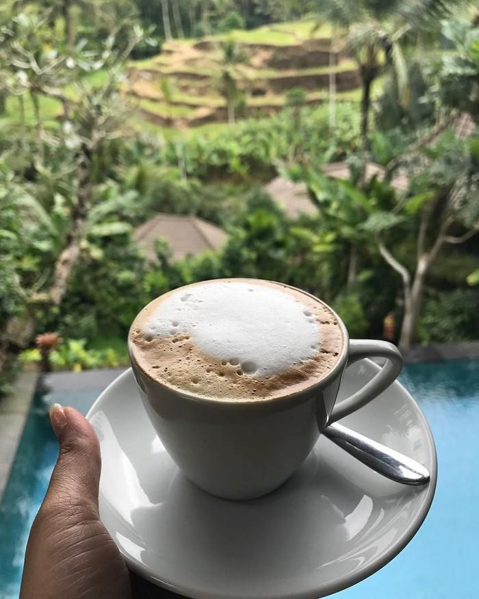 Donna sedang menikmati coffee with a view nih. Secangkir kopi hangat difoto dengan latar hijau pemandangan sawah dan birunya air di kolam renang. Foto: Instagram @dagnesia