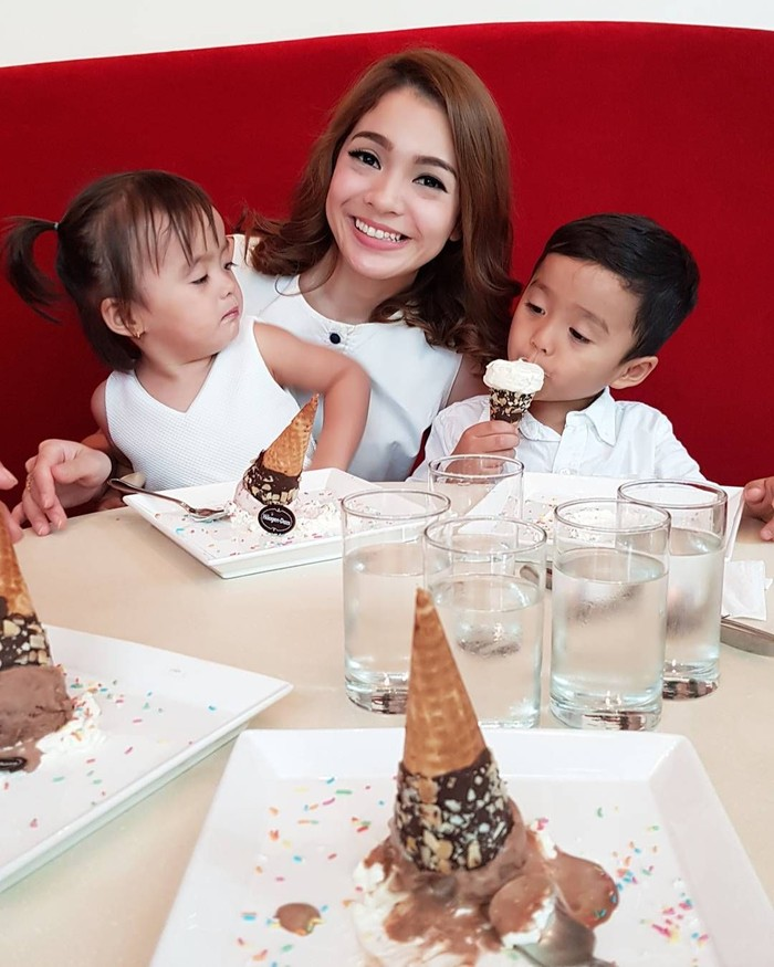 Bersama kedua anaknya, Devon dan Kathleen, Maya Sedang menikmati es krim. Tapi dua es krim di depannya untuk suster dua anaknya lho. Salut! Foto: Instagram mayaseptha7