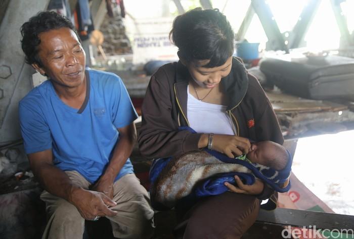 Meskipun tinggal di kolong jembatan dengan biaya hidup harian pas-pasan, Mahmud (43) dan Jannah (17) tampak bahagia dengan kehadiran Khaidar Ali yang baru berusia 10 hari. Foto: Agung Pambudhy/detikHealth