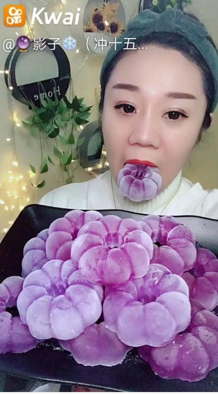 Lihat es batu bentuk bunga berwarna ungu ini. Wanita itu tanpa ragu menggigit dan menyunyahnya, lho! Foto: Istimewa